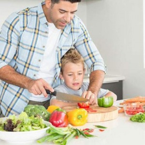 father teaching son how to cut vegetables
